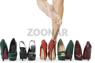 Woman Legs in Red Shoes Between Other High Heels