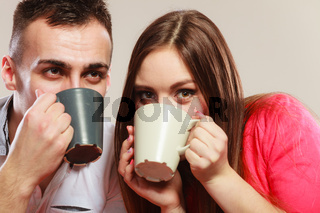 young couple holds mugs with tea or coffee