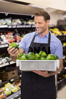 Smiling handsome worker taking a box with vegetable