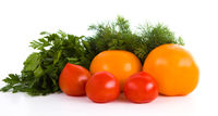 Red and yellow tomatoes with dill and parsley isolated on white