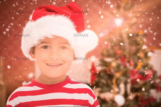 Composite image of cute little boy in santa hat