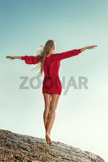 Woman in long dress in front of sea