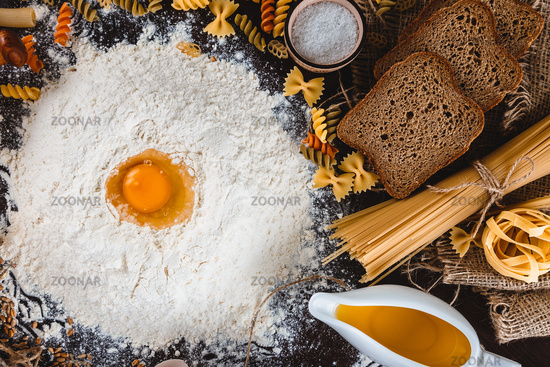 Pasta on dark wooden background with eggs, oil and flour close-up macro