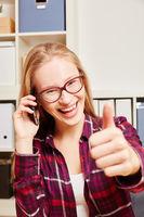 Frau hält Daumen hoch beim Telefonieren