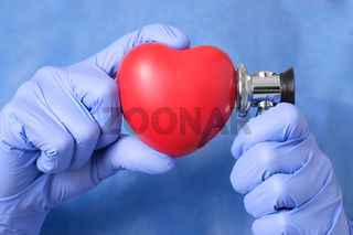 Red heart and stethoscope in the hand of a doctor