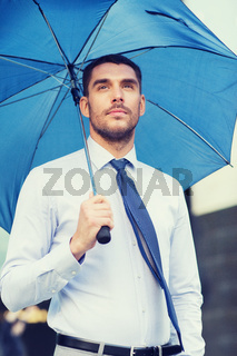 young serious businessman with umbrella outdoors