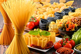 Composition with variety of pasta on kitchen table.