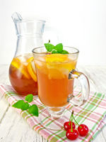 Lemonade with cherry in wineglass and pitcher on board