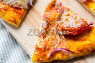 close up of homemade pizza slice on wooden table