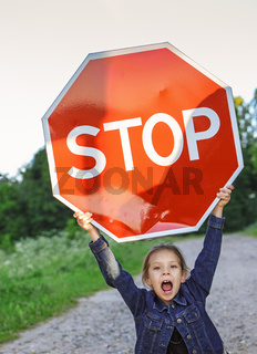 little girl holding a red sign 'STOP'