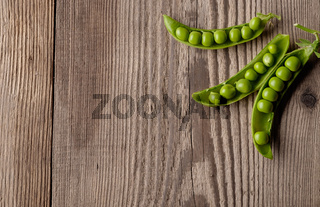 Ripe Green peas on wooden table.