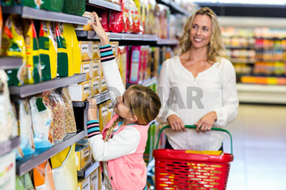 Cute daughter taking food from shelf