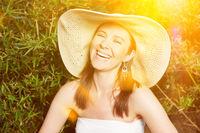Lachende Frau mit Strohhut im Sommer