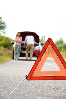 Adult man and women near broken car