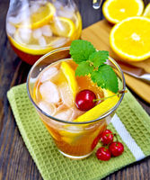 Lemonade with cherry in glassful and pitcher on board