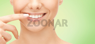 close up of smiling woman face pointing to teeth