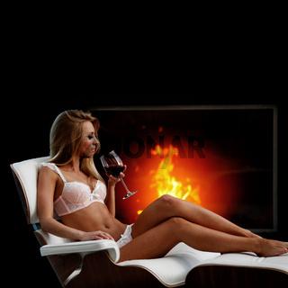 Woman with wine near fireplace