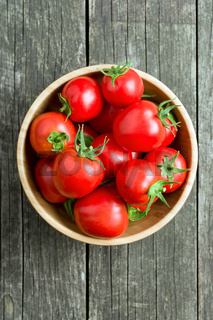 red tomatoes in wooden bowl