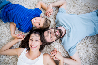 Portrait of parents and son lying on rug
