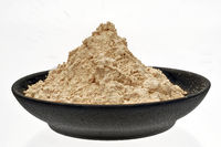Superfood maca powder in a black bowl on a white surface for cropping.