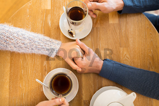 close up of couple holding hands at restaurant