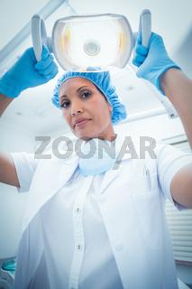 Serious female dentist adjusting light