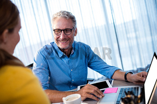 Two businessmen interacting and smiling