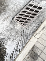 water from heavy rain flows into a sewer drain