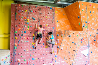 Fit women rock climbing indoors