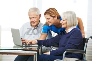 Frau zeigt Senioren Internet am Computer