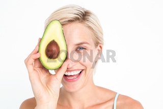 Pretty woman covering her eye with an avocado