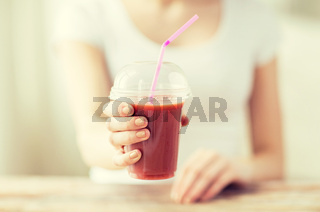 close up of woman holding cup with smoothie