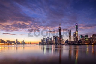 waterfront cityscape and illuminated skyline at dawn