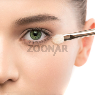 Young brunette woman with clean face. Girl perfect skin applying cosmetic brush. Isolated on white.