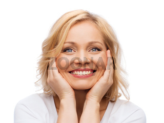 smiling woman in white t-shirt touching her face