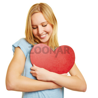 Junge Frau umarmt ein rotes Herz aus Liebe