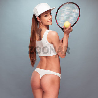 Sexy Female Tennis Player Holding Racket and Ball