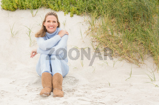 Smiling woman sitting on the sand