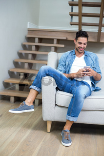 Man using smartphone while sitting on sofa