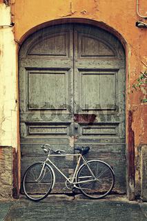 Bicycle against old wooden door.