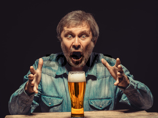 The screaming man in denim shirt with glass of beer