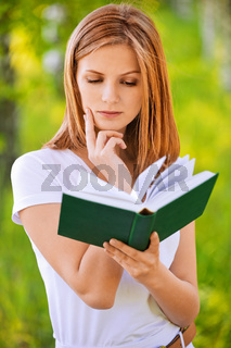 portrait of beautiful young blond woman with book