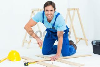 Happy repairman fixing screw on plank