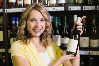 Portrait of a smiling pretty blonde woman showing a wine bottle