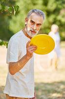 Alter Mann mit einer Frisbee Scheibe