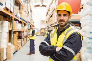 Smiling worker wearing yellow vest with arms crossed