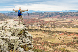 hiker on rocky cliff overlooking valley
