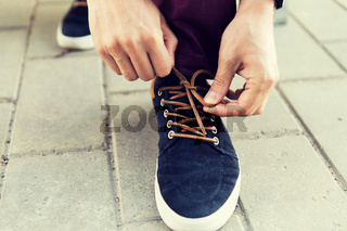 close up of male hands tying shoe laces on street