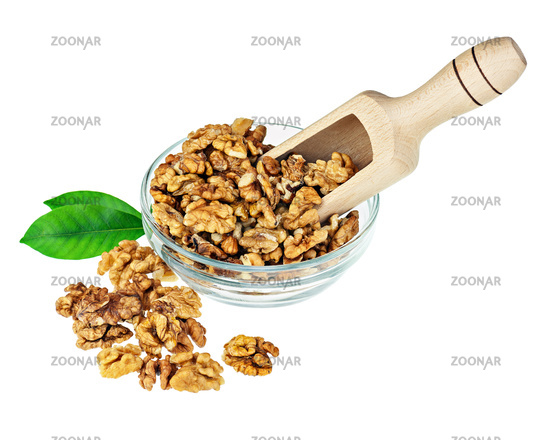 Handful of walnuts in glass bowl, scoop and green leaves.
