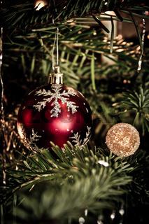 Matt rote Christbaumkugel mit Schneeflockenmuster am Weihnachtsbaum